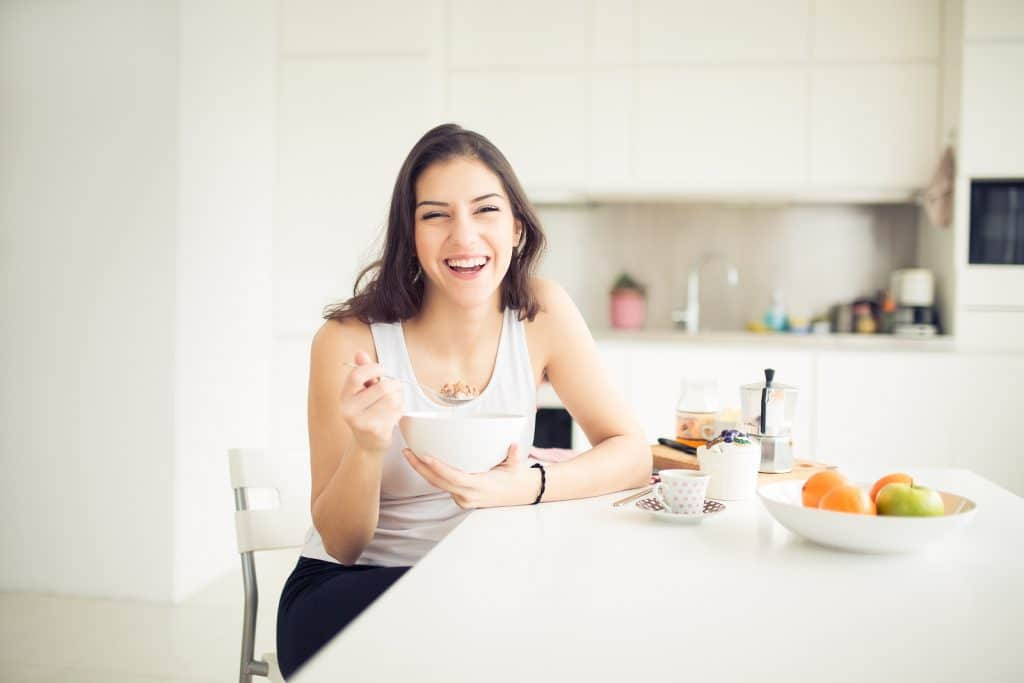 Young smiling woman eating cereal and smiling.Healthy breakfast.Starting your day.Dieting,fitness and wellbeing.Positive energy and emotion.Productivity,happiness,enjoyment concept.Morning ritual