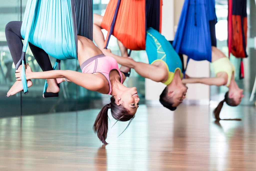 Side view of a fit and beautiful young woman hanging upside down while practicing aerial yoga during group class in a modern fitness club