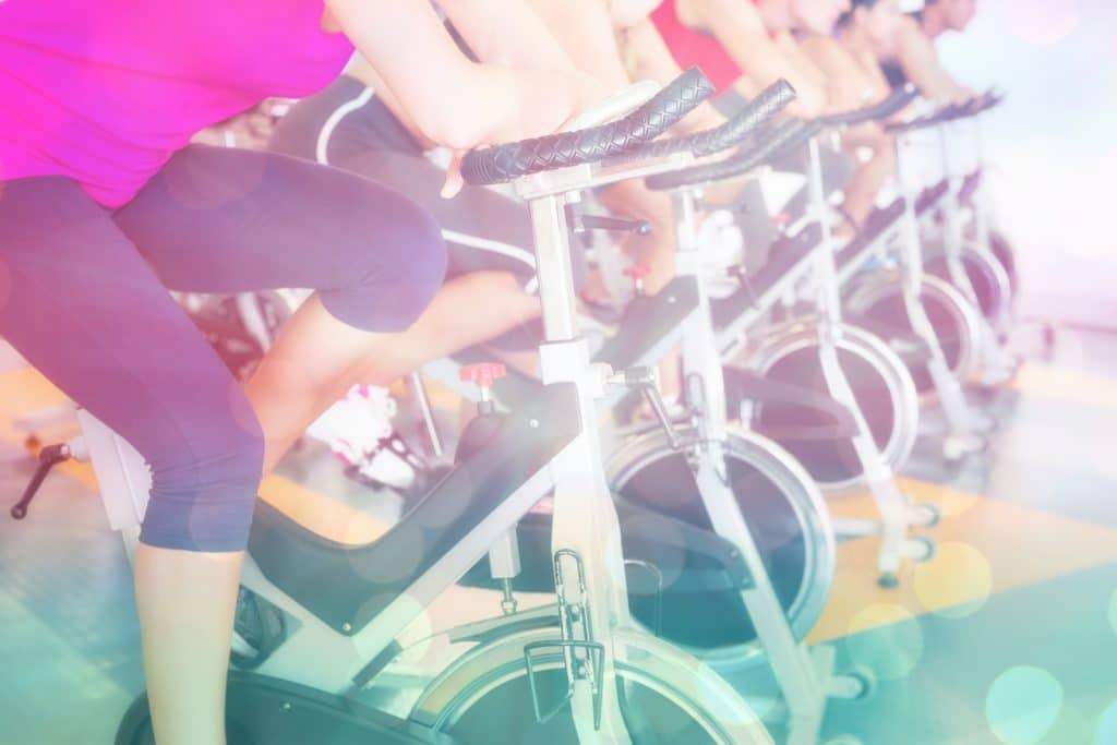 Spin class working out in a row against abstract background