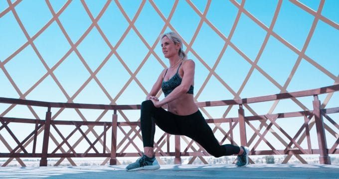 Woman in green sports bra doing lunges