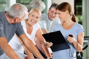 Happy seniors with fitness trainer in a gym