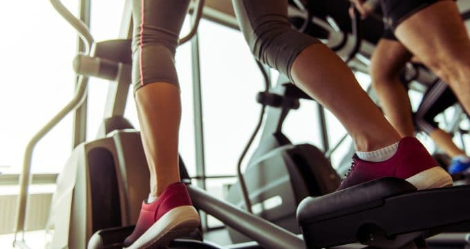 Back view of attractive young people working out on an elliptical trainer in gym