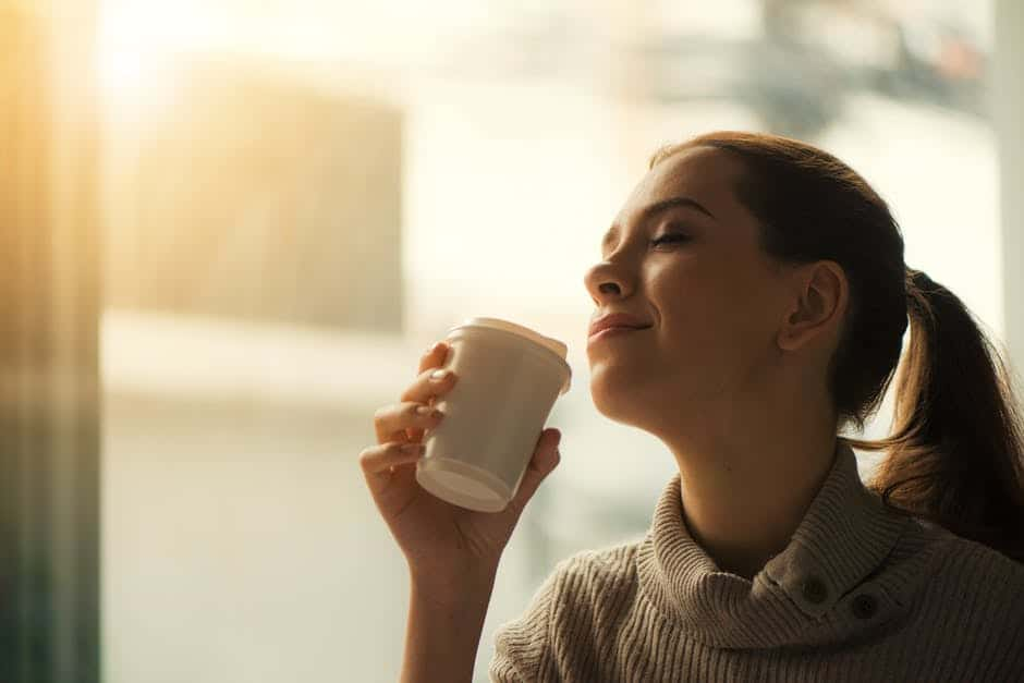 woman smelling what inside her cup