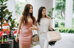 two women carrying a handbag and taking a walk