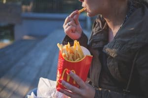a person eating French fries from a famous fast food chain