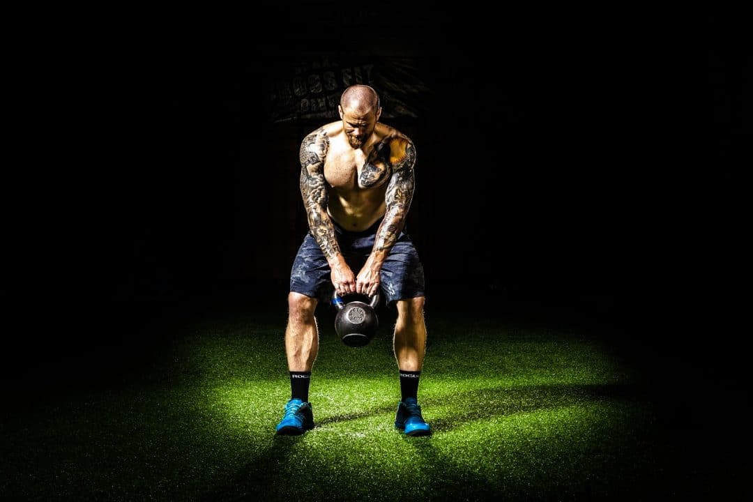 Shirtless man holding a kettlebell