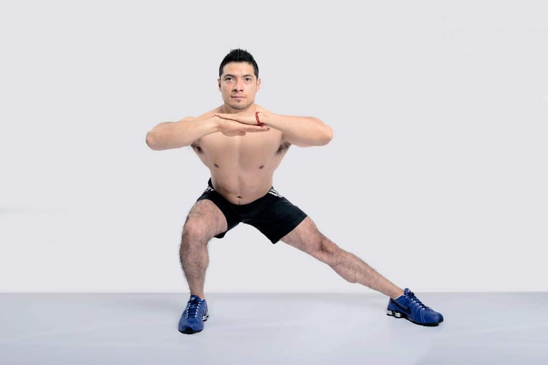 Shirtless man doing lunges